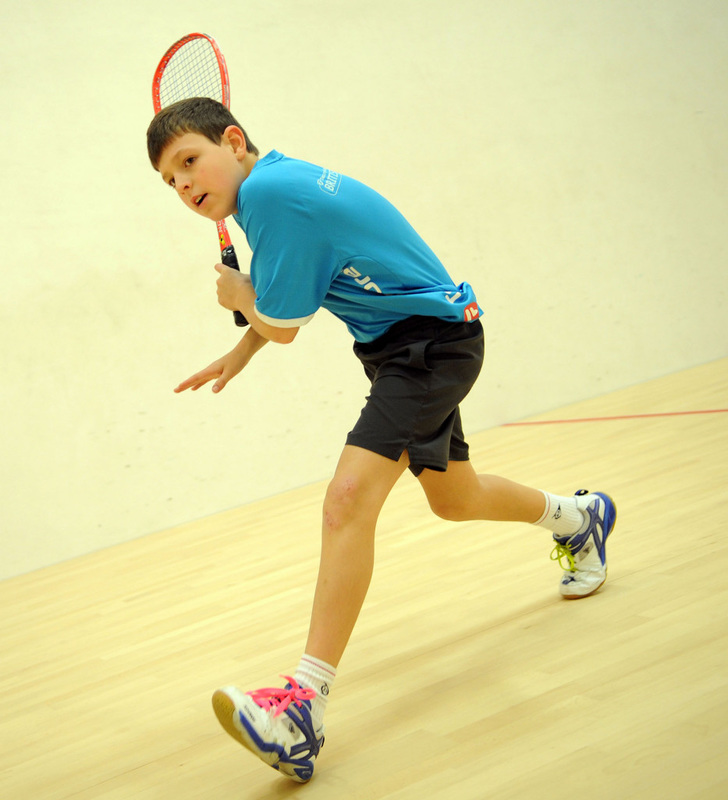 A junior squash player swings his racket on the squash court in DC