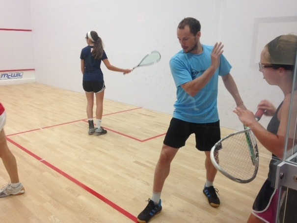 Photo of Greg Gaultier instructing juniors squash players on a squash court at Squash Revolution