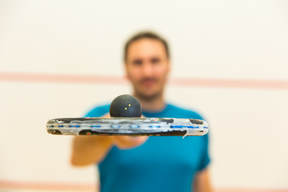 A squash coach holding a squash racket and ball on the court